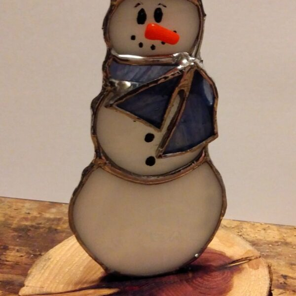 Snowman with scarf and hat on cedar